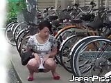 Tantalizing Japanese girl peeing in front of someone bicycle