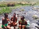 Busty topless African girls singing in river